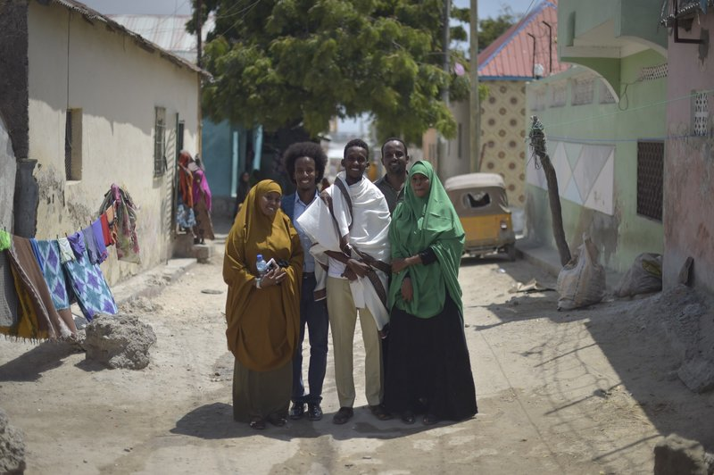 Mohamed Hussein Hassan (second from left), Chairman of City Flowers — an NGO which organizes events and aims to celebrate the beauty of their city — and his team on a road outside their offices in Mogadishu, Somalia. Their projects include city clean-ups,