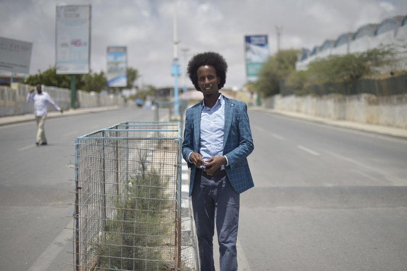 Mohamed Hussein Hassan, Chairman of City Flowers, next to one of the trees planted by his organization in Mogadishu. Their projects include city clean-ups, planting trees along the capital's roads, and painting cross walks at busy intersections.