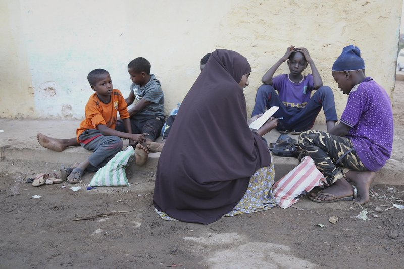 Jamila Haji Mohamed (centre), Chairwoman of the Mis-Hurty Arlaathey organization, takes the contact information of children living on the streets of Baidoa, Somalia. Jamila has helped enroll street children in formal schools.