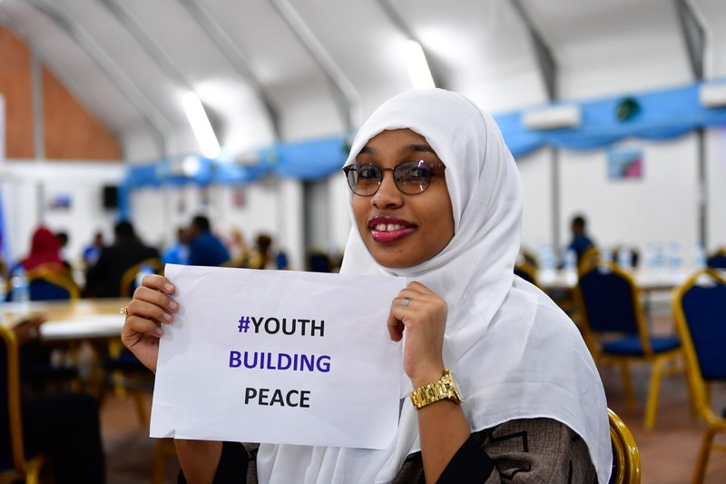 A Somali youth holds a peace message at a ceremony to mark International Youth Day, held in Mogadishu on August 12, 2017. Somali youths have become proactive in peace-building initiatives in various parts of the country.