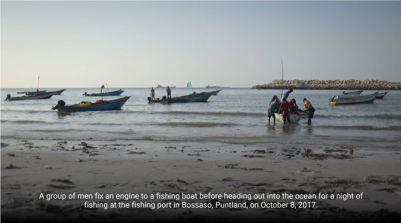A group of men fix an engine to a fishing boat before heading out into the ocean for a night of fishing at the fishing port in Bossaso, Puntland, on October 8, 2017.