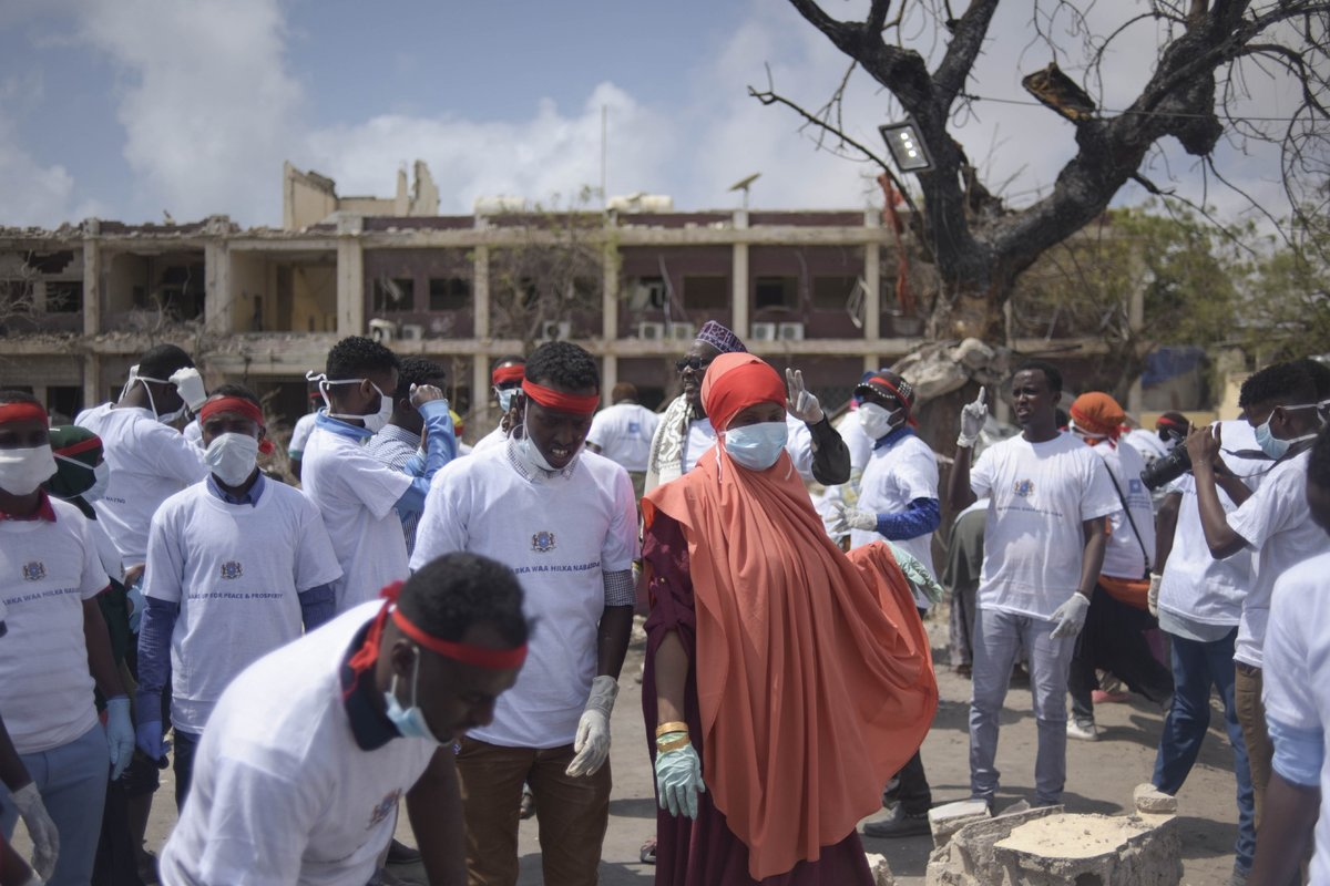 Students from various universities in Mogadishu, Somalia, who came together under the umbrella group 'Gurman Qaran' help in the cleanup effort at the scene of the explosion that killed more than 300 people in the capital on 14 October 2017.